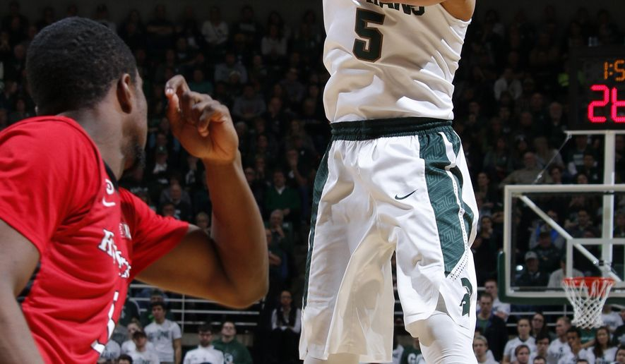 Michigan State's Bryn Forbes, right, passes against Rutgers' Mike Williams during the first half of an NCAA college basketball game, Sunday, Jan. 31, 2016, in East Lansing, Mich. (AP Photo/Al Goldis)