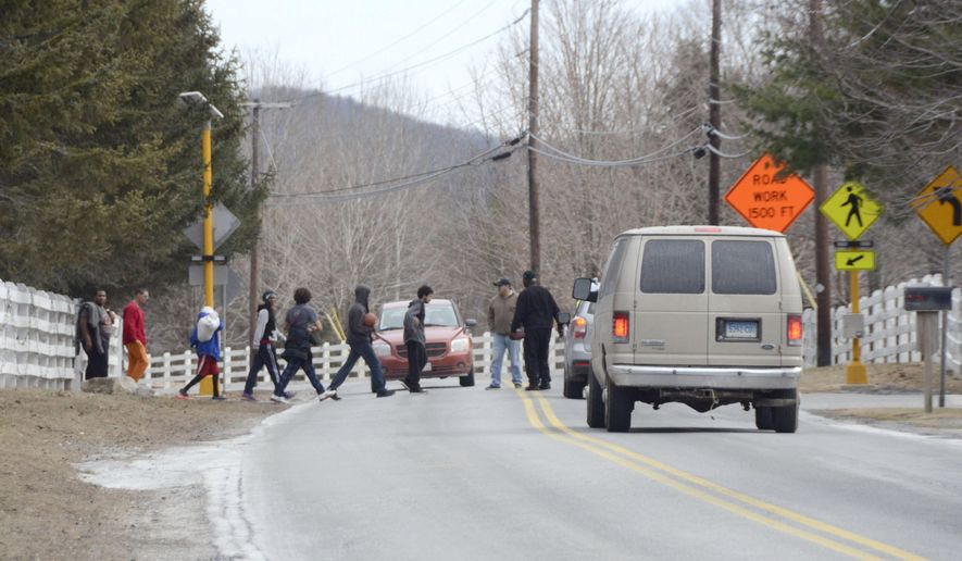 Students cross Monterey Road at Eagleton School in Great Barrington, Mass. on Sunday, Jan. 31, 2016, following a search at the school on Saturday by some 50 local, state and federal law enforcement officers. The school is facing allegations of physical and emotional abuse on students by staff at the school. (Gillian Jones/The Berkshire Eagle via AP)