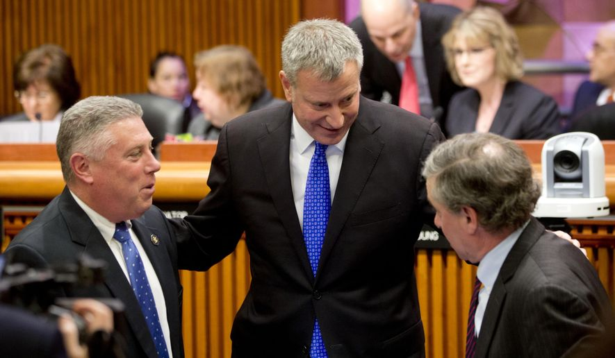 FILE - In this Jan. 26, 2016, file photo, New York City Mayor Bill de Blasio, center, talks with Assemblymen John McDonald III, D-Albany, left, and  Steven Otis, D-Port Chester, before testifying at a joint legislative budget hearing hearing on local government in Albany, N.Y. A new state budget proposal is reigniting an old debate over whether New York City deserves special treatment from state leaders in Albany. (AP Photo/Mike Groll, File)