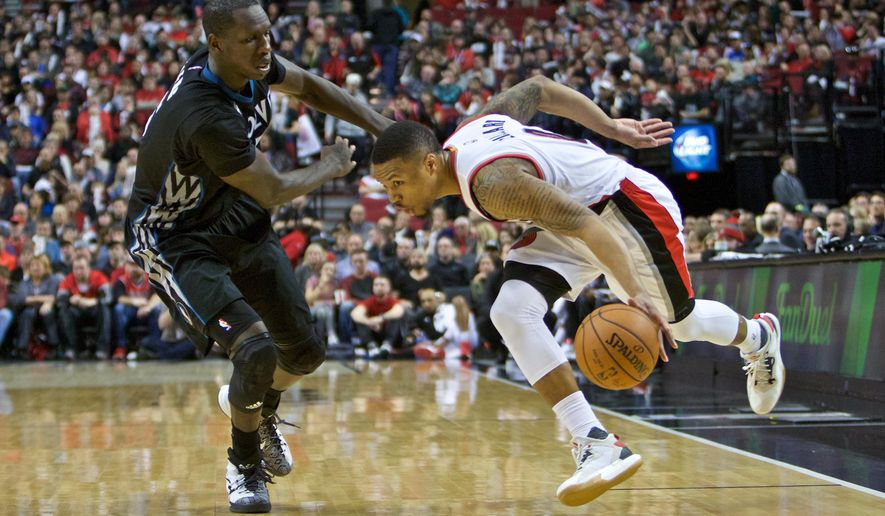 Portland Trail Blazers guard Damian Lillard, right, dribbles round Minnesota Timberwolves center Gorgui Dieng, left, during the second half of an NBA basketball game in Portland, Ore., Sunday, Jan. 31, 2016. The Trail Blazers won 96-93. (AP Photo/Craig Mitchelldyer)