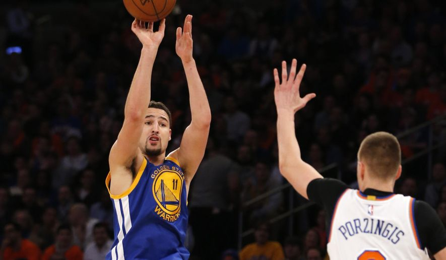 Golden State Warriors guard Klay Thompson (11) shoots as New York Knicks forward Kristaps Porzingis (6) defends in the first half of an NBA basketball game at Madison Square Garden in New York, Sunday, Jan. 31, 2016. (AP Photo/Kathy Willens)