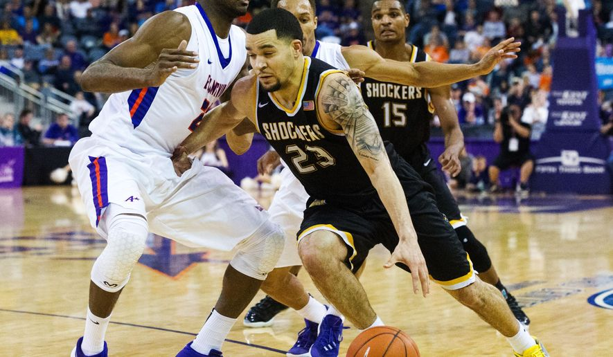 Wichita State's Fred Vanvleet (23) drives the ball through UE's Willie Wiley (23) and Jaylon Brown (3) in the second half of an NCAA college basketball game Sunday, Jan. 31, 2016, in Evansville, Ind. Wichita State won, 78-65. (AP Photo/Daniel R. Patmore)