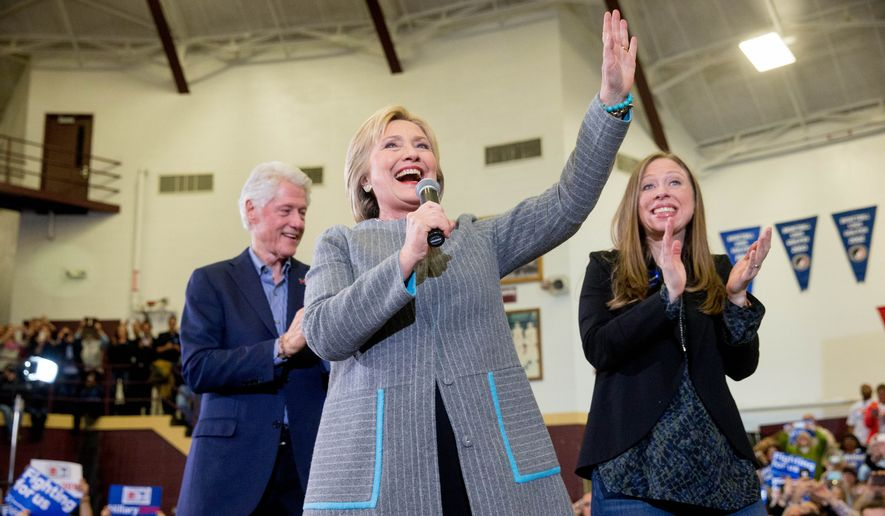 Democratic presidential candidate Hillary Clinton, accompanied by her husband, former President Bill Clinton and their daughter Chelsea Clinton, waves as she arrives to speak at a rally at Abraham Lincoln High School in Des Moines, Iowa, Sunday, Jan. 31, 2016. (AP Photo/Andrew Harnik)