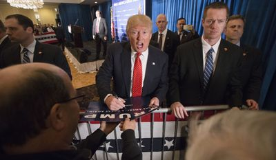 Republican presidential candidate Donald Trump signs autographs during a campaign stop at the Radisson Hotel, Friday, Jan. 29, 2016, in Nashua, N.H. (AP Photo/John Minchillo)