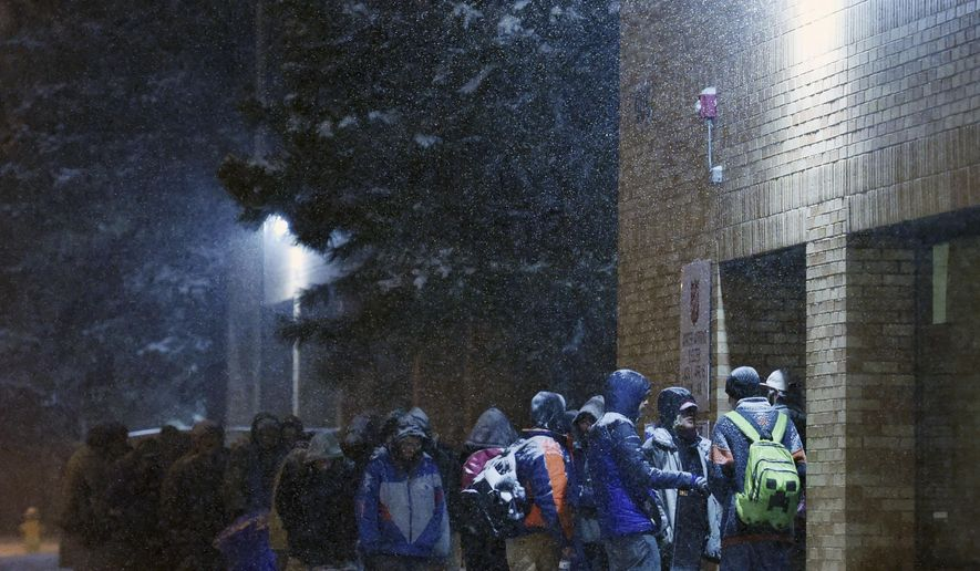 A line of people forms in front of Salvation Army Warming Shelter in Colorado Springs, Colo., Sunday, Jan. 31, 2016. Because of worsening conditions, the doors of the shelter were opened an hour early for those who would have to spend the night outside, according to the The Gazette. Most of Colorado is under a winter storm warning as a storm bears down on the state. (Jerilee Bennett/The Gazette via AP) MAGS OUT; MANDATORY CREDIT