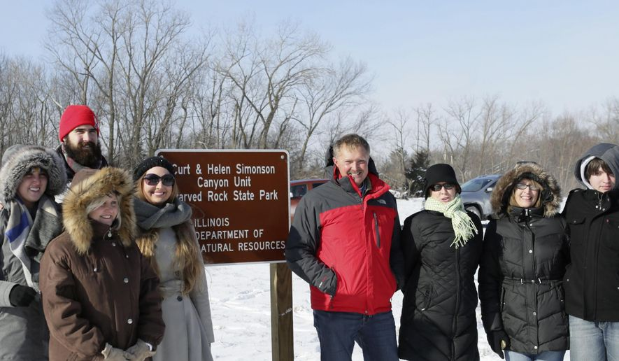 In this Jan. 12, 2016 photo, members of the Simonson family pose near the sign of the newly dedicated Curt and Helen Simonson Canyon Unit at Starved Rock State Park near Utica, Ill.. The former site of the White Oaks Campground, the land was formally dedicated at a ceremony by Illinois Department of Natural Resources director Wayne Rosenthal. From left are: Carrie Jennings, Dawn Swanson, Mike Jennings, Sarah Cunniff, Curtis Simonson, Chris Simonson, Laurie Cunniff and Ryne Cunniff. (Chris Yucus/NewsTribune via AP) MANDATORY CREDIT