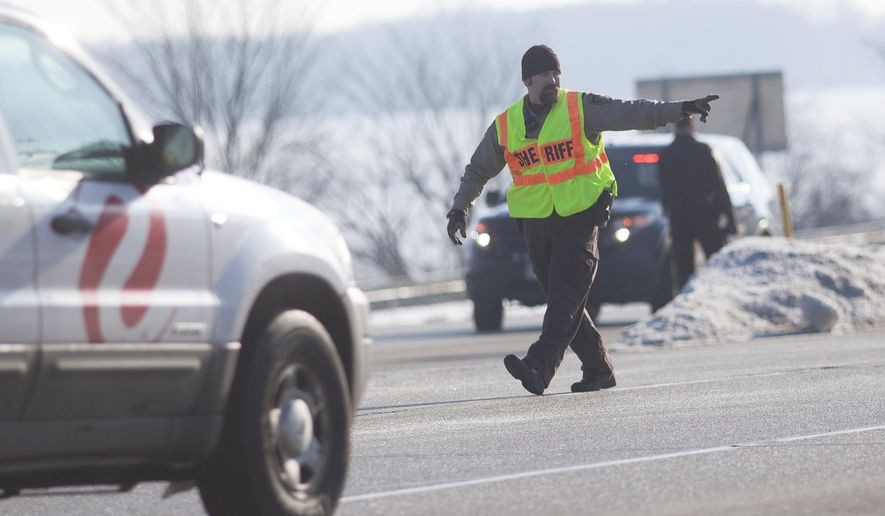 A member of the Winona County Sheriff Department directs traffic on Highway 61 South following a fatal vehicle accident on Monday, Feb. 1, 2016, in Winona County, Minn. (Chuck Miller/The Winona Daily News via AP) MANDATORY CREDIT