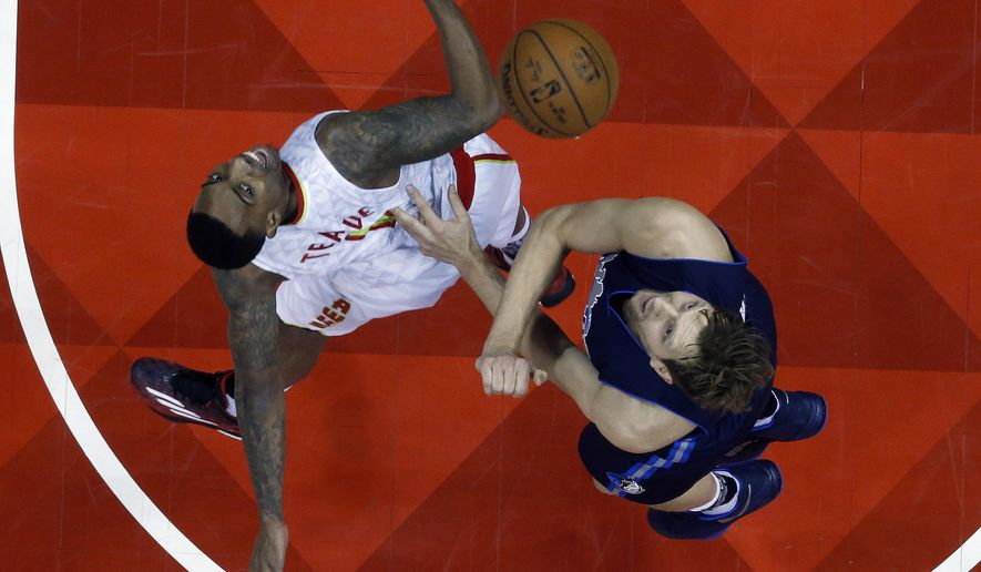 Atlanta Hawks guard Jeff Teague (0) and Dallas Mavericks forward Dirk Nowitzki (41) battle for a rebound in the first half of an NBA basketball game Monday, Feb. 1, 2016, in Atlanta. (AP Photo/John Bazemore)