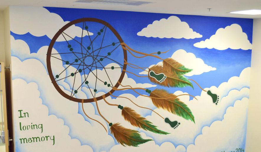 In this 2014 photo provided by Lindsay Fuori, a mural she created to pay tribute to Sandy Hook Elementary School shooting victims adorns a wall inside Newtown High School, which she attended. The mural was covered by plasterboard to protect the emotional well-being of students. (Lindsay Fuori via AP)