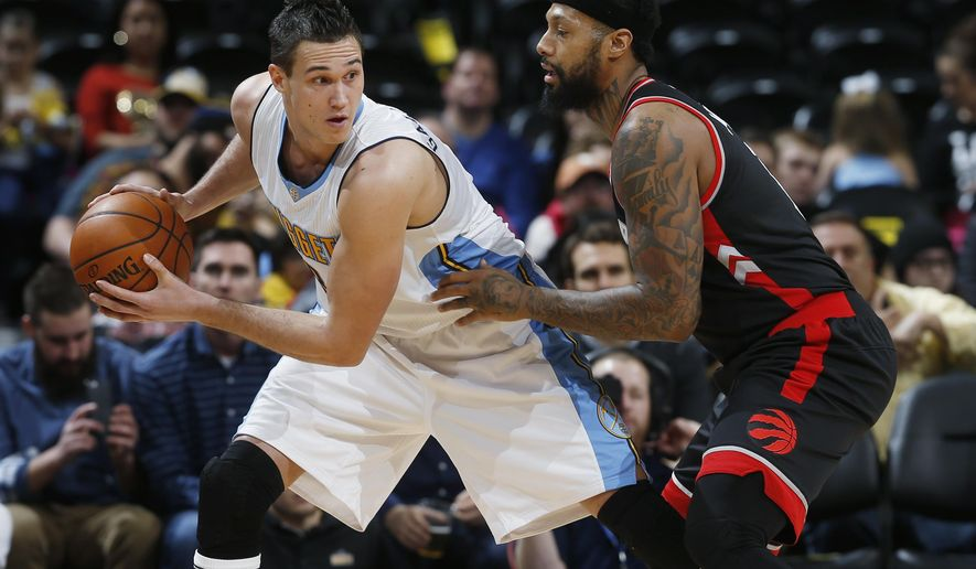 Denver Nuggets forward Danilo Gallinari, left, of Italy, looks to pass the ball as Toronto Raptors forward James Johnson defends in the first half of an NBA basketball game Monday, Feb. 1, 2016, in Denver. (AP Photo/David Zalubowski)