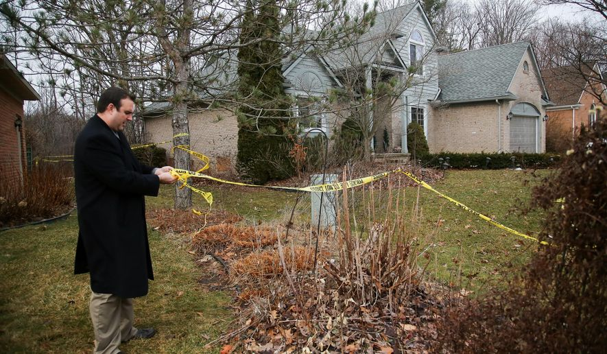 A Novi police detective secures the police tape around a home where five Mexican immigrants died in a weekend house fire, Tuesday, Feb. 2, 2016, in Detroit. (Kimberly P. Mitchell/Detroit Free Press via AP)  DETROIT NEWS OUT; TV OUT; MAGS OUT; NO SALES; MANDATORY CREDIT DETROIT FREE PRESS