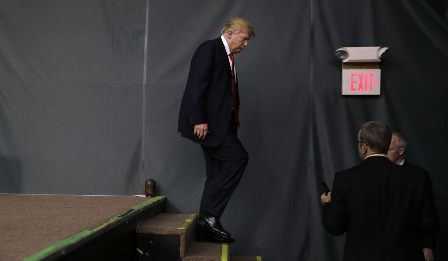 Republican presidential candidate Donald Trump walks down the steps after speaking at a caucus site, Monday, Feb. 1, 2016, in Clive, Iowa. (AP Photo/Jae C. Hong)