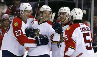 Florida Panthers center Nick Bjugstad (27), center Jonathan Huberdeau (11), right wing Reilly Smith (18) and defenseman Aaron Ekblad (5) celebrate a goal by Huberdeau during the second period of an NHL hockey game against the Washington Capitals, Tuesday, Feb. 2, 2016, in Washington. (AP Photo/Alex Brandon)