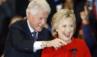 Former President Bill Clinton, left, and Democratic presidential candidate Hillary Clinton acknowledge supporters during a caucus night rally at Drake University in Des Moines, Iowa, Monday, Feb. 1, 2016. (AP Photo/Patrick Semansky)