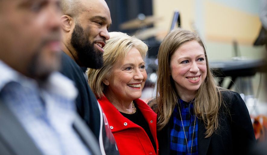 Democratic presidential candidate Hillary Clinton, center, and her daughter Chelsea Clinton, right, pose for a photograph with visitors to the African American Festival, I'll Make Me a World Celebration Day at the Iowa Events Center in Des Moines, Iowa, Saturday, Jan. 30, 2016. (AP Photo/Andrew Harnik)