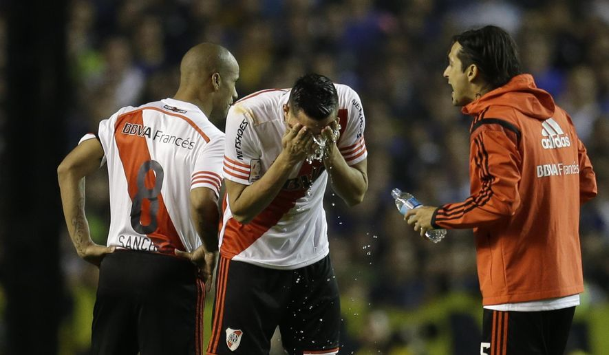 """FILE - In this May 14, 2015 file photo, Ramiro Funes Mori of Argentina's River Plate, center, and teammates wash their faces after pepper spray was sprayed at them from the stands, at the start of the second half of a Copa Libertadores soccer match against Boca Juniors in Buenos Aires, Argentina. On Tuesday, Feb. 2, 2016, Conmebol reduced sanctions against Boca Juniors from eight games closed to the public, to two, calling it a """"measure of grace."""" (AP Photo/Victor R. Caivano, File)"""