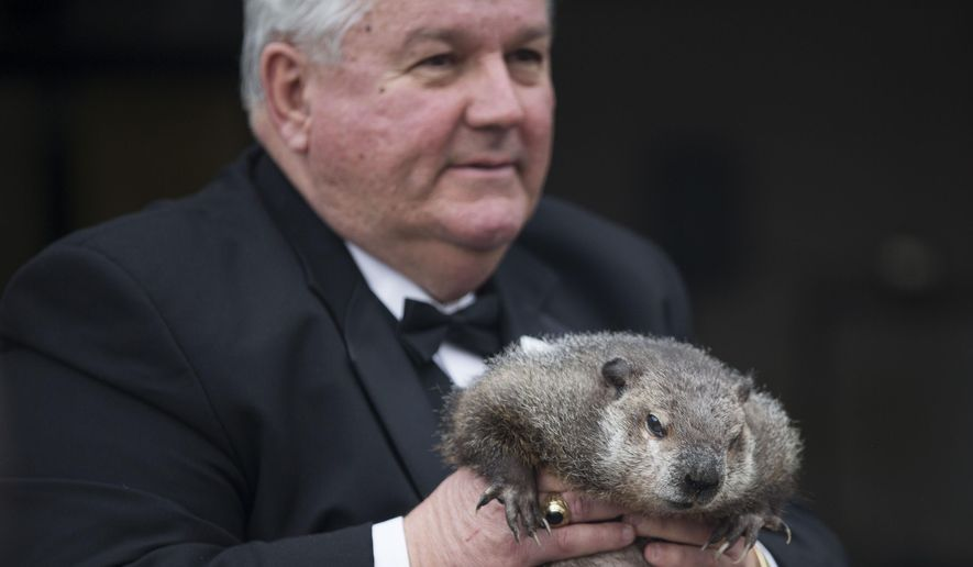Inner Circle President Bill Deeley shows Punxsutawney Phil to tourists a day before Groundhog Day in Punxsutawney, Pa., on Monday, Feb. 1, 2016. (Mark Pynes/PennLive.com via AP)