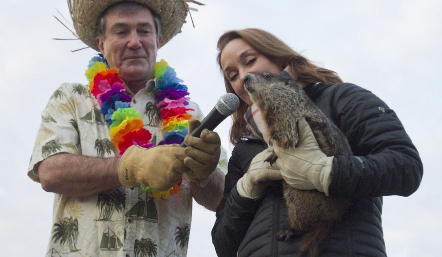 Howell Conference and Nature Center director Dick Grant, dressed for an early spring, and wildlife director Dana DeBenham, dressed for more winter introduce Woody before putting her inside her prediction shack, from which she wouldn't emerge, Tuesday, Feb. 2, 2016, in Marion Township, Mich. The groundhog predicted six more weeks of winter. (Gillis Benedict /Livingston County Daily Press & Argus via AP)  NO SALES; MANDATORY CREDIT