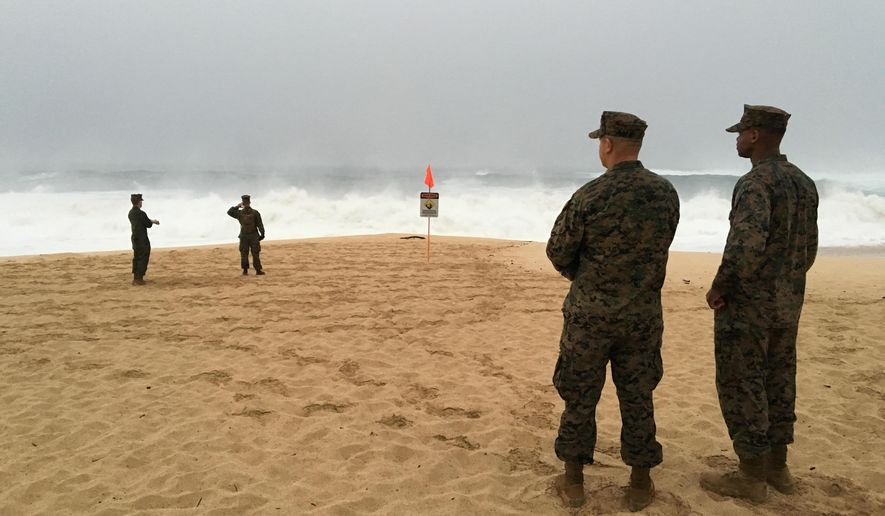 FILE - This Jan. 15, 2016 file photo shows U.S. Marines walking on the beach at Waimea Bay in Haleiwa, Hawaii, close to where two military helicopters crashed into the ocean. The U.S. Marine Corps said Tuesday, Feb. 2, that trace elements of DNA have been found from Marines killed in a helicopter crash off Hawaii last month. (Mariana Keller via AP Photo)