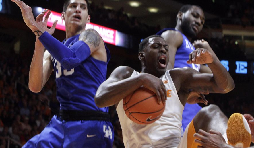 Tennessee forward Armani Moore (4) grabs a rebound ahead of Kentucky forward Derek Willis, left, and guard Jamal Murray during the first half of an NCAA college basketball game Tuesday, Feb. 2, 2016, in Knoxville, Tenn. (AP Photo/Wade Payne)