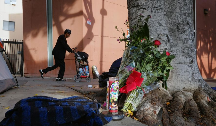 FILE - This March 2, 2015 file photo shows a pedestrian walks past flowers and candles placed on a sidewalk near where Charly Keunang a homeless man was shot and killed by police in the Skid Row section of downtown Los Angeles. An oversight panel is deliberating whether Los Angeles police officers were justified in the fatal shooting of a homeless black man in Skid Row. (AP Photo/Richard Vogel,File)