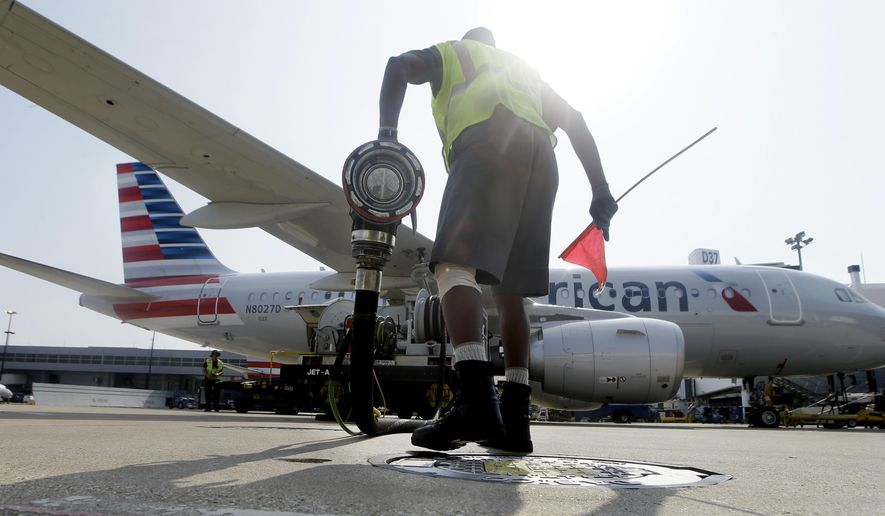 FILE - In this Thursday, Aug. 26, 2015, file photo, Scott Mills finishes fueling up an American Airlines jet at Dallas/Fort Worth International Airport in Grapevine, Texas. Cheap oil will be sticking around for a while. Businesses such as airlines that burn large amounts of fuel have reaped savings in the billions. But energy company profits have plunged, as have their stocks. Layoffs and spending cuts by oil drillers have offset some of the boost from steady consumer spending. (AP Photo/LM Otero, File)