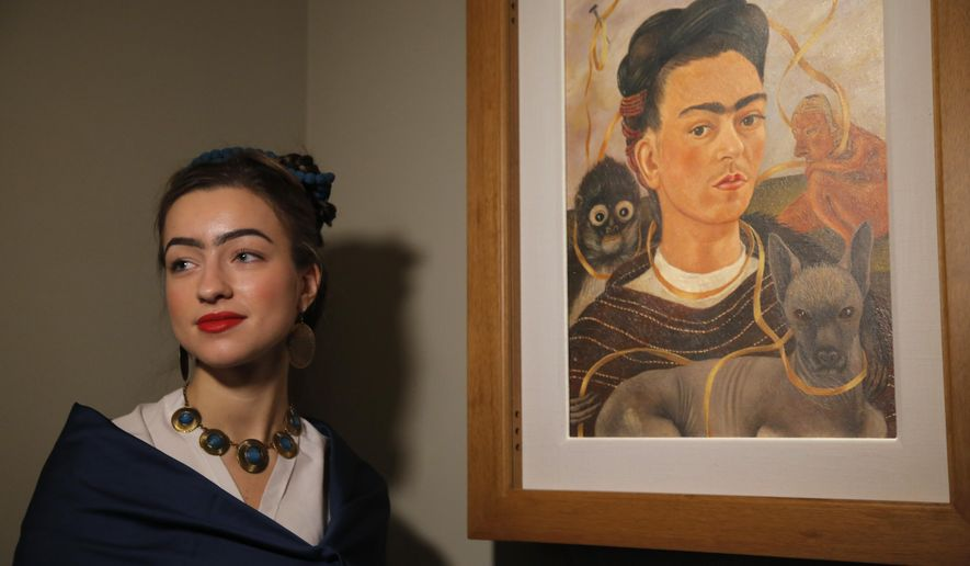 A visitor stylised as Frida Kahlo poses for photo next to a Frida's Kahlo self-portrait at the Frida Kahlo exhibition in St.Petersburg, Russia, Tuesday, Feb. 2, 2016. A retrospective exhibition of the renowned Mexican artist Frida Kahlo started on Tuesday at the Faberge Museum. This is the first Frida Kahlo exposition of such scale in Russia. The exhibition features 34 works, including paintings, drawings and lithographs. (AP Photo/Dmitry Lovetsky)
