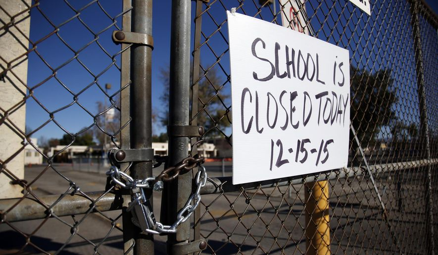"FILE - In this Dec. 15, 2015, file photo, a gate to Birmingham Community Charter High School in Van Nuys, Calif., is locked with a sign stating that school is closed following an electronic threat to the Los Angeles Unified School District. Hoaxers are increasingly going online to threaten attacks against U.S. schools. The threats are a type of ""swatting,"" reporting a phony emergency to bring SWAT teams rushing to the scene. (AP Photo/Danny Moloshok, File)"
