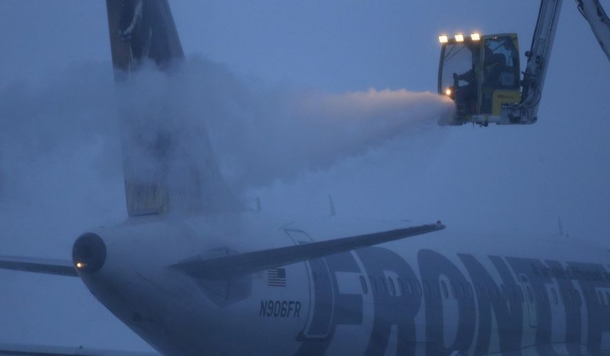 A deicing team prepares a commercial jet for safe flight during severe weather at Denver International Airport, in Colorado, early Tuesday, Feb. 2, 2016. A powerful winter storm has shut down highways in eastern Colorado, closed many schools and slowed down traffic at Denver International Airport. (AP Photo/Brennan Linsley)