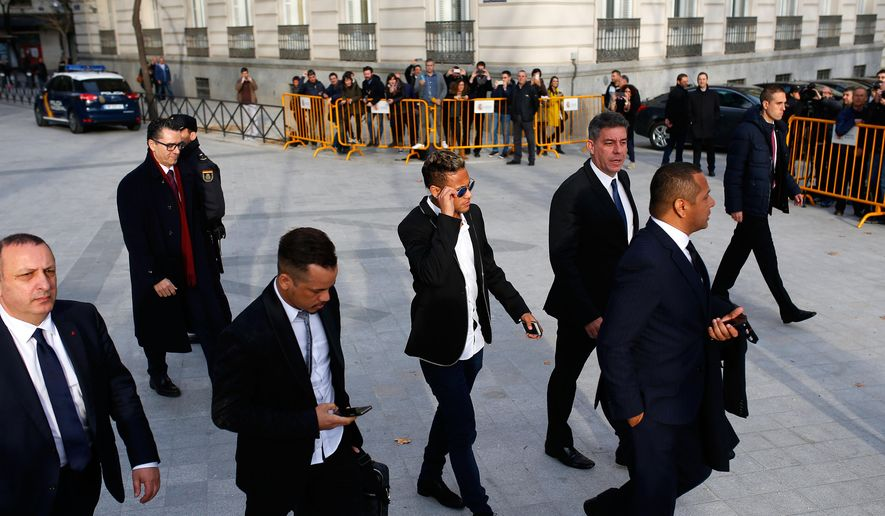 FC Barcelona's Neymar, center, arrives to the national court to testify in an investigation into alleged irregularities regarding his transfer to Barcelona, in Madrid, Tuesday, Feb. 2, 2016. The court is looking into a complaint made by a Brazilian investment group which claims it was financially harmed when Barcelona and Neymar allegedly withheld the real amount of the player's transfer fee from Brazilian club Santos in 2013. (AP Photo/Francisco Seco)
