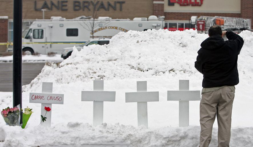 FILE - In this Feb. 3, 2008 file photo, Greg Zanis, of Sugar Grove, Ill., puts up five crosses and leaves flowers as police investigate the fatal shooting of five women the previous day at the Lane Bryant store at the Brookside Shopping Center in Tinley Park, Ill. Eight years later, police say they believe there are people out there who know the killer's identity. Since the slayings on Feb. 2, 2008, investigators with the Tinley Park Police Department have received nearly 7,000 leads, and they still continue to regularly get tips. (AP Photo/Jerry Lai, File)