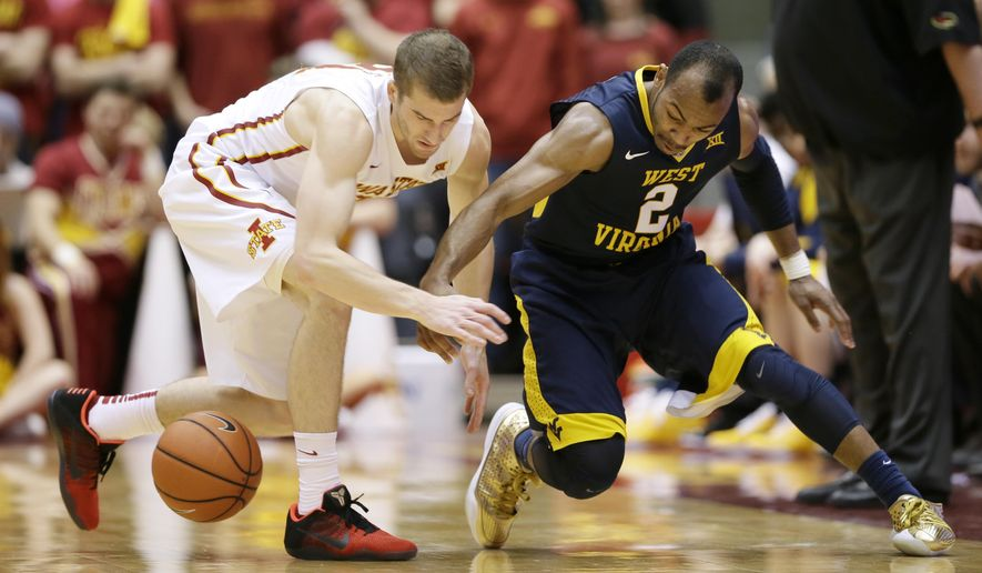 Iowa State guard Matt Thomas, left, fights for a loose ball with West Virginia guard Jevon Carter, right, during the first half of an NCAA college basketball game Tuesday, Feb. 2, 2016, in Ames, Iowa. (AP Photo/Charlie Neibergall)