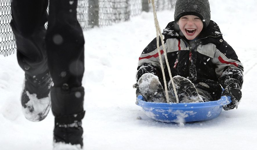 Oscar Perrin gets a pull on a sled by his mother Heather on a snowy sidewalk in Boulder, Colo., Monday, Feb. 1, 2016. (Paul Aiken/Daily Camera via AP) MANDATORY CREDIT