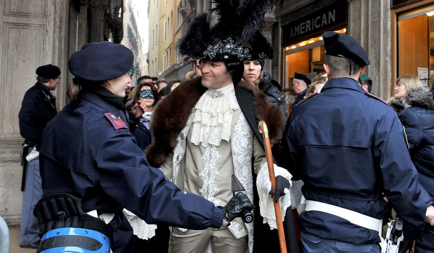 A Police officer inspects a man wearing a carnival costume in Venice, Italy, Sunday, Jan. 31, 2016. People attended the Venice Carnival, celebrated Saturday under heightened security following the sexual assaults on New Year's Eve in Cologne and the ongoing terror threat in Europe. Authorities have increased surveillance throughout the city, including the number of officers on patrol, both under-cover and in uniform. (AP Photo/Luigi Costantini)
