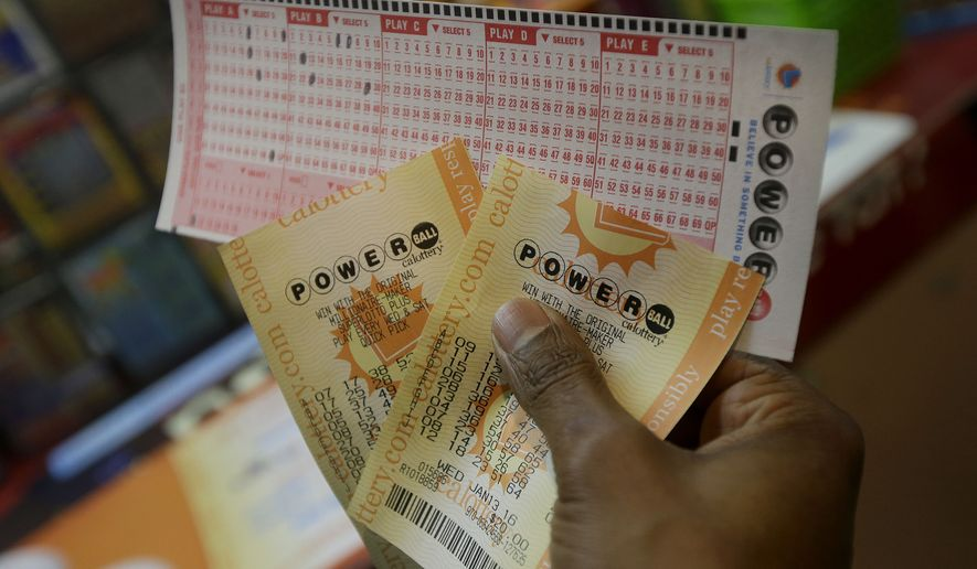 Duane Bouligny holds up Powerball tickets he purchased at Moza Easy Shop in San Francisco, Wednesday, Jan. 13, 2016. The Powerball jackpot for Wednesday night's drawing is at least $1.5 billion, the largest lottery jackpot in the world. (AP Photo/Jeff Chiu)