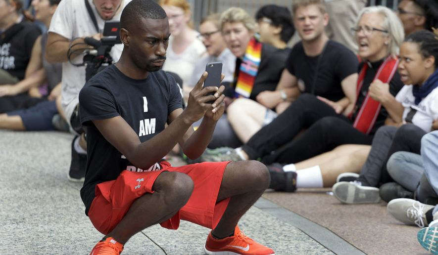 FILE - In an Aug. 10, 2015 file photo, protester and social media activist DeRay McKesson records outside the Thomas F. Eagleton Federal Courthouse Monday, in St. Louis. Mckesson has joined the crowded 2016 Baltimore mayoral race. Maryland's State Board of Elections shows that he filed Wednesday, Jan. 3, 2016, to run in the Democratic primary along with 12 other candidates. (AP Photo/Jeff Roberson, File)
