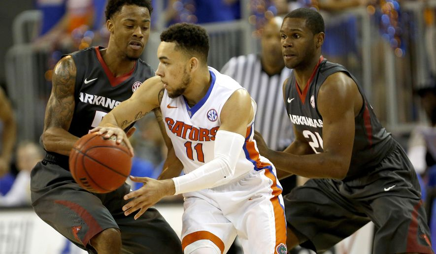 Florida guard Chris Chiozza (11) looks to pass around full-court pressure by Arkansas guard Anthlon Bell (5) and guard Manuale Watkins (21) during the first half of an NCAA college basketball game at the O'Connell Center on Wednesday, Feb. 3, 2016 in Gainesville, Fla. (Matt Stamey/The Gainesville Sun via AP)  THE INDEPENDENT FLORIDA ALLIGATOR OUT; MANDATORY CREDIT