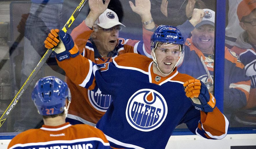 Edmonton Oilers' Connor McDavid (97) and Adam Clendening (27) celebrate McDavid's goal against the Columbus Blue Jackets during the second period of an NHL hockey game in Edmonton, Alberta, Tuesday, Feb. 2, 2016.  (Jason Franson/The Canadian Press via AP) MANDATORY CREDIT