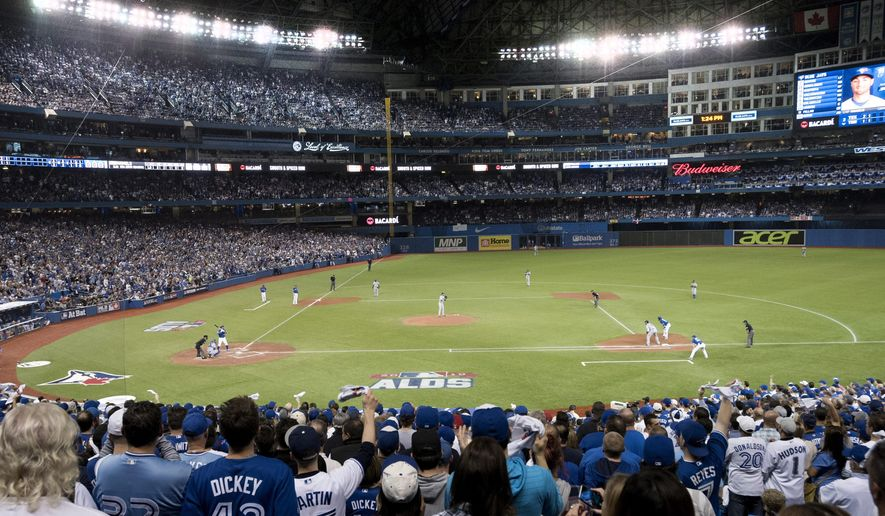 FILE - In this Oct. 9, 2015, file photo, the Toronto Blue Jays and the Texas Rangers play during the first inning of Game 2 of an AL division series in Toronto. The Blue Jays are installing a dirt infield at the Rogers Centre for the first time but say it is too early to determine whether they would replace artificial turf with grass in some future season. (Darren Calabrese/The Canadian Press via AP, File)