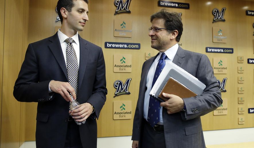 FILE - In this Sept. 21, 2015, file pjoto, Milwaukee Brewers general manager David Stearns,left, talks to owner Mark Attanasio at a news conference in Milwaukee. When Attanasio checks in with Stearns, he likes to test him like a fan about the team's latest moves. The start of the rebuilding process has been tough for the competitive owner. (AP Photo/Morry Gash, File)