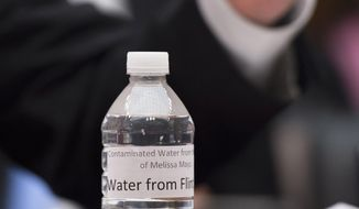 "A bottle of ""water from Flint"" sits in front of Rep. Dan Kildee, D-Mich. as he testifies on Capitol Hill in Washington, Wednesday, Feb.  3, 2016, before the House Oversight and Government Reform Committee hearing to examine the ongoing situation in Flint, Mich. Flint is under a public health emergency after its drinking water became tainted when the city switched from the Detroit system and began drawing from the Flint River in April 2014 to save money. The city was under state management at the time. (Associated Press) **FILE**"