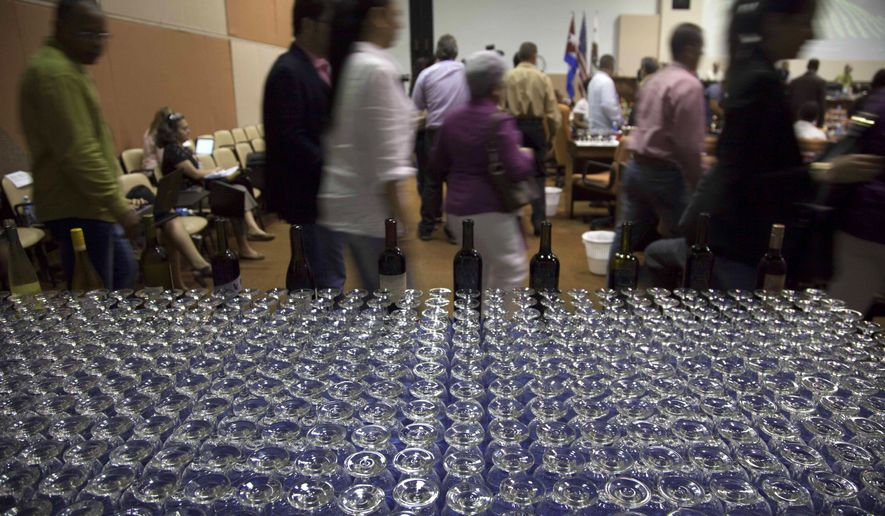People attend the first California Wine Symposium in Havana, Cuba, Tuesday, Feb. 2, 2016. In a sign of changing times, California's largest winemakers hold a two-day tasting and trade show for Cuban restaurant owners in hopes of developing a new market in a country dominated by rum, weak beer and cheap South American wine. (Ismael Francisco/Cubadebate via AP)