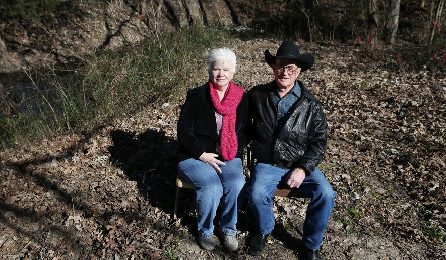 "In this Jan. 27, 2016 photo, Billy Pemberton, right, and his wife, Zada Pemberton, sit for a portrait in front of a natural spring called ""Big Spring"" on what used to be their property in Dallas. The Dallas Morning News reports that the preservation designation being voted on Monday, Feb. 1, includes rules meant to prevent major alterations to the site. (Andy Jacobsohn/The Dallas Morning News via AP) MANDATORY CREDIT; MAGS OUT; TV OUT; INTERNET USE BY AP MEMBERS ONLY; NO SALES"