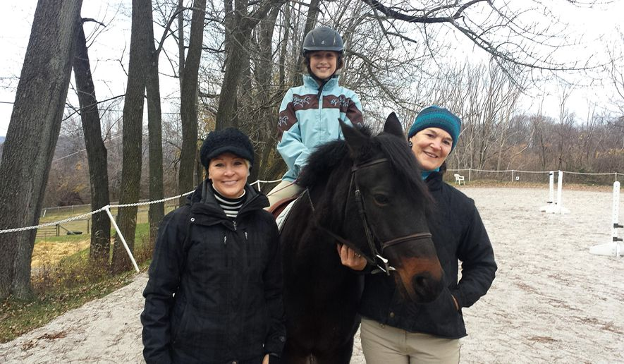 In this Nov. 24, 2015, photo, the president of Horse Power for Life, Shiree Radie, left, riding student and volunteer Zoe Moumoutgis, center, and riding instructor Becca Smith, right, pose with a horse on Stone Crop Farm in Glenmoore, Pa. Horse Power for Life offers a discounted 16-week therapeutic horsemanship program for men, women and children diagnosed with cancer, and more than 200 people have participated in the program since the nonprofit organization's 2007 founding. (Michilea Patterson/The Mercury via AP) PHILLY METRO OUT