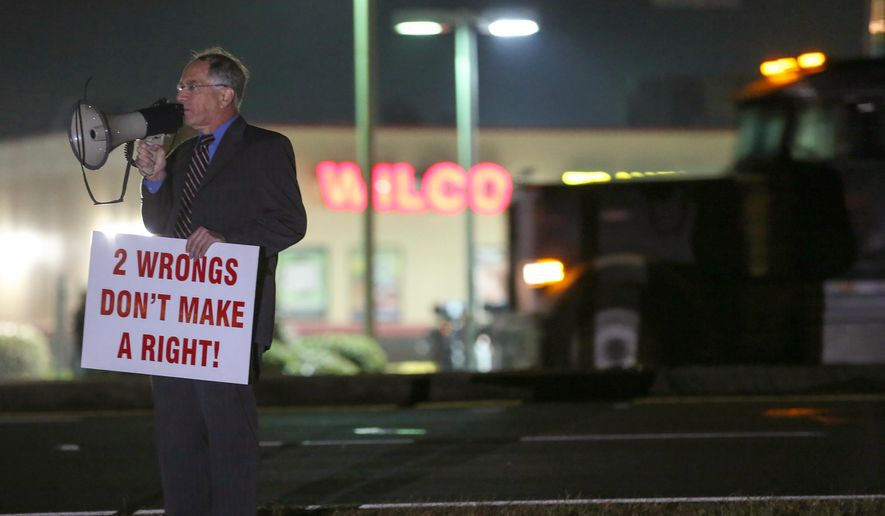 Attorney Daniel Kolber uses a megaphone to voice his opposition to the death penalty while standing just outside the Georgia Diagnostic and Classification State Prison grounds in Jackson, Ga., Tuesday, Feb. 2, 2016. (Ben Gray/Atlanta Journal-Constitution via AP)