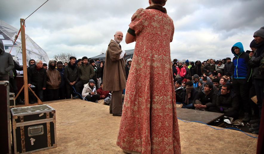 """Actors perform Hamlet, Wednesday Feb.3, 2016 in the refugees camp of Calais, northern France. The Globe theater company took """"Hamlet"""" to Calais , bringing one of Shakespeare's best-known plays to an audience that almost certainly would rather see it in his native country. The play is hosted by the Good Chance theater in the heart of the camp, one of numerous structures set up by volunteers to fill the void for its displaced residents. (AP Photo/Thibault Camus)"""