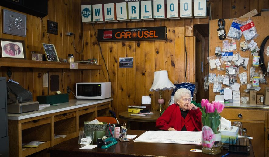 Mary Ann Gorzenski sits at her desk Monday, Feb. 1,2016,  at Joe's Appliance Store, in Bay City, Mich. She received tulips for her recent 100 year birthday. (Yfat Yossifor/The Bay City Times via AP)