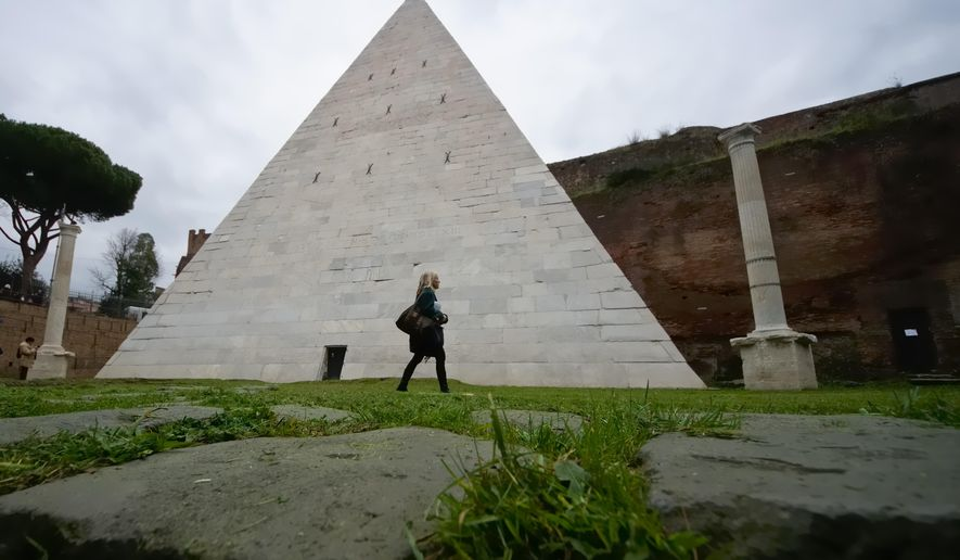 A woman walks past the Pyramid of Cestius in Rome, Wednesday, Feb. 3, 2016. Rome's only surviving pyramid from ancient times is getting fresh visibility. After a Japanese clothing magnate paid for a cleanup, archaeologists are eager to show off the monument, constructed some 2,000 years ago as the burial tomb for a Roman praetor, or magistrate, named Caius Cestius. (AP Photo/Domenico Stinellis)
