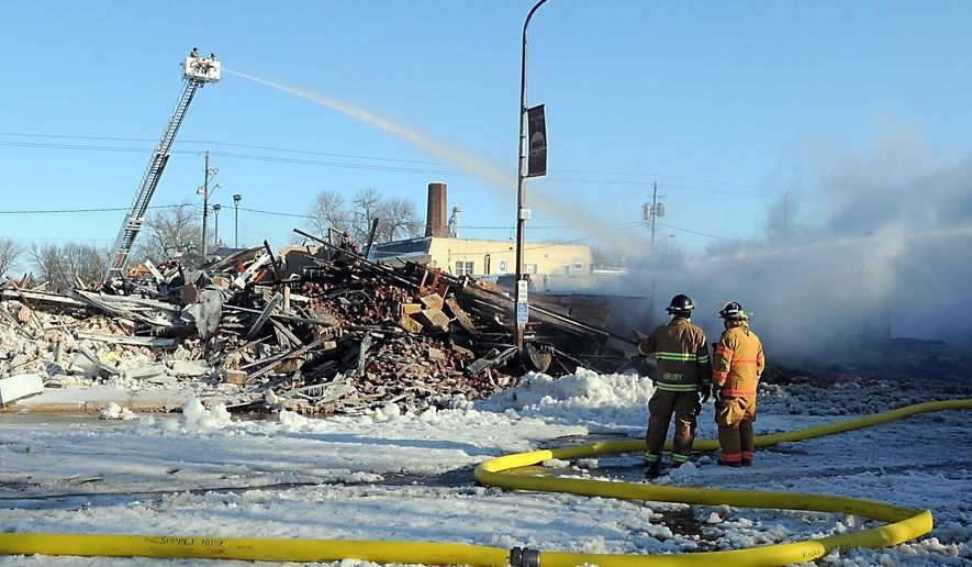 Firefighters spray water on the remains of one of the buildings destroyed by an early morning fire in downtown Madelia, Minn. Wednesday, Feb. 3, 2016. The fire took out about two-thirds of the businesses on one side of Main Street, city administrator Jane Piepgras said. There were no immediate reports of injuries. (Pat Christman/The Free Press via AP) MANDATORY CREDIT