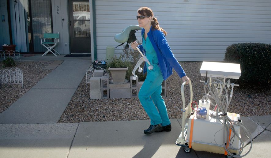 Jenna Mayerhofer, a dental hygienist for Dental Care In Your Home,  wheels in a cart with dental equipment toward the home of a client for a cleaning, Friday, Jan. 22, 2016, in Albuquerque, N.M.  Dental professionals are hitting the road in vans as part of an Albuquerque health care program that treats hundreds of elderly in their homes and at assisted living centers.  (Marla Brose/The Albuquerque Journal via AP) MANDATORY CREDIT